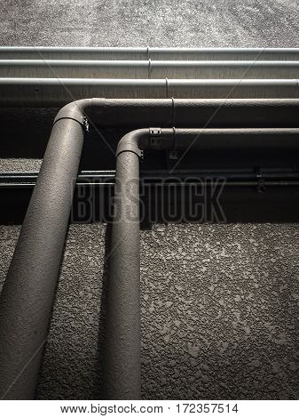 Dark grey old steel or metal pipes on rough wall background.