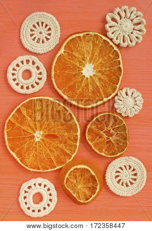 Dry oranges and white vintage elements of Irish crochet. Doilies circle coasters creative craft work food design