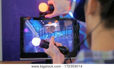 Virtual reality game. Young man using virtual reality glasses and hand controlers