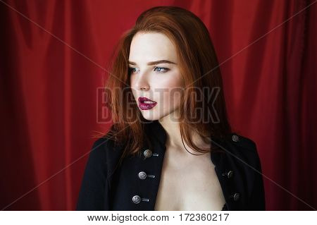 Beautiful red-haired girl with parted lips in black lingerie on red background looking away. Fashion photography. Bright appearance. Red hair. Woman posing hands