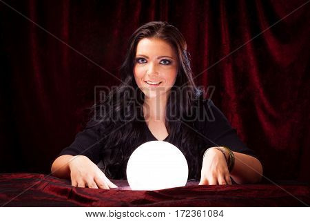 Studio shot of friendly fortune teller with crystal ball