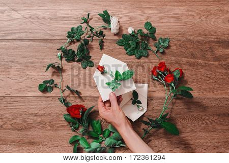 Hand holding white envelope. Envelope and a white and red rose. Greeting card. Conceptual photography. Wedding invitation card. Valentine day. Flat lay top view copyspace