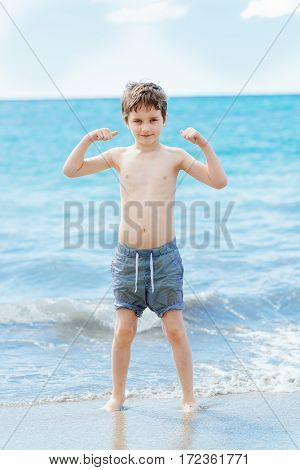 Happy 7 Years Boy In Victory Success Gesture On The Beach.