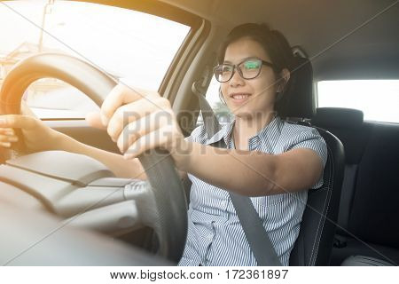 Asian glasses woman holding on steering wheel while driving a car with sunlight. Soft focus.