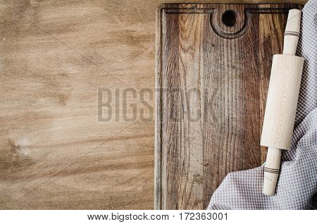 Kitchen Background: Rolling-pin with Kitchen Towel or Napkin on Wooden Board Over the Rustic Wooden Table. View From Above With Copy Space