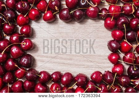 Ripe red cherries lie on a wooden background. Frame of ripe summer berries. Space for text copyspace