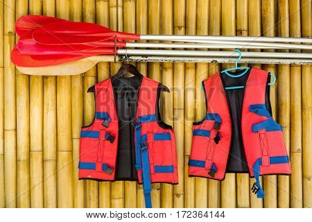 red life jacket and oars on a wall of bamboo.