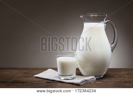 glass and jug full of milk on wooden table