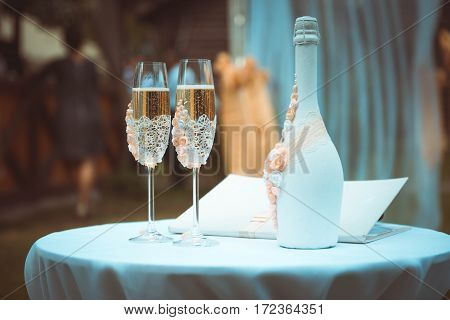 Two beautiful wine glasses with champagne and decorated bottle on wedding day.