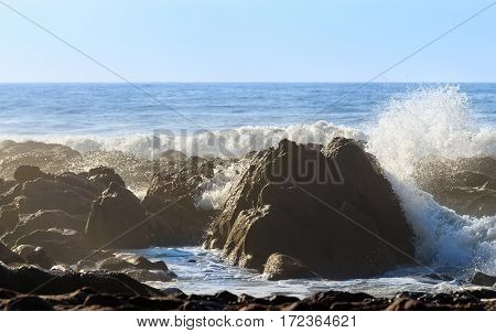 Beautiful big rock on oceanic beach with big waves and water splashes.