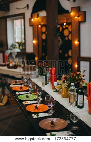 Wedding banquet table with dishes, vine and food. Loft, country and rustic style. Decoration. Arch with bulb garland on background