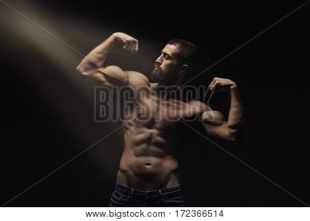 studio portrait of athlete bodybuilder man isolated over black background. Dramatic light from above