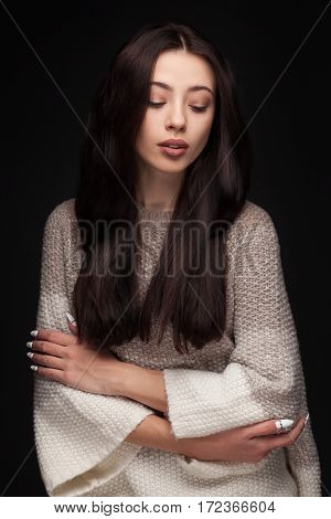 portrait of young elegant woman with long brown hair wearing knitted sweater on black background