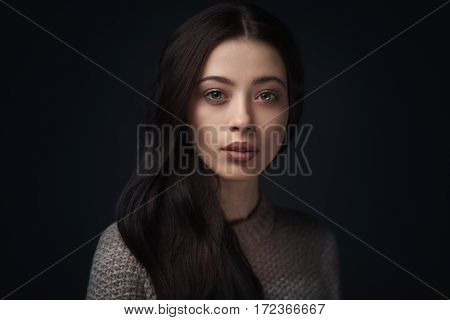 closeup portrait of young elegant woman with long brown hair wearing knitted sweater on black background