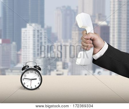 Hand Holding Telephone Handset With Alarm Clock