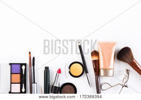 Makeup cosmetics, brushes and other essentials border on white background. Top view, flat lay with copy space. Beauty tools collection, lipstick, eyeshadow, eyelash curler, foundation and more