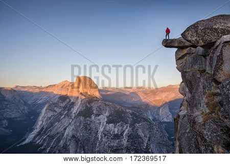 A male hiker is standing on an overhanging rock at Glacier Point enjoying the breathtaking view towards famous Half Dome in beautiful twilight at sunset in summer Yosemite National Park California