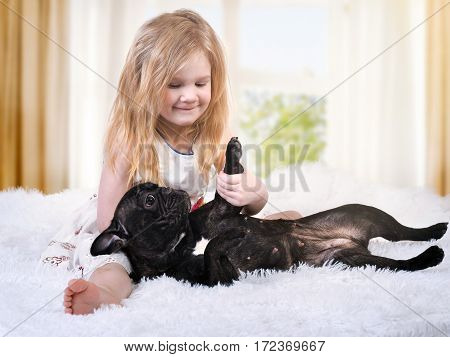 Little girl playing with a dog on the bed. The child and pet are happy together. White fluffy blanket light room