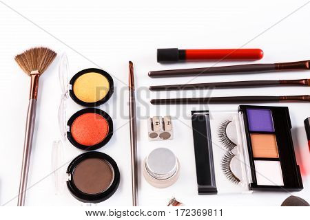 Makeup cosmetics, brushes and other essentials on white background. Flat lay with copy space. Multicolored beauty tools and products collection, lipsticks, eyeshadow, mascara, sponge, eyelash