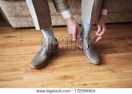 The man wears shoes. Tie the laces on the shoes. Men's style. Professions. To prepare for work to the meeting.