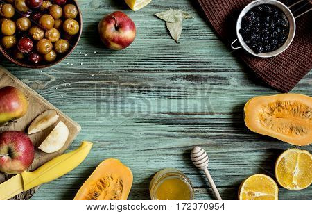 fruit and honey in a pot on the aged turquoise rough wooden table top view