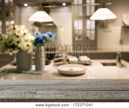 Blurred background. Modern kitchen with tabletop and space for you. Empty wooden table and blurred kitchen background for display or montage your products