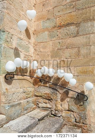 For a wedding is the entrance of a church in Largentiere in the Ardeche region of France decorated with white heart-shaped balloons