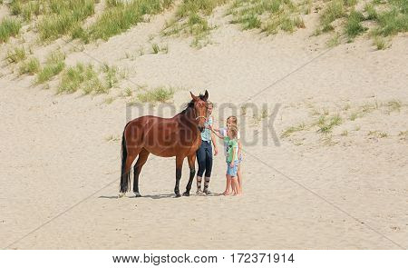 Texel, Netherlands, August 1, 2015: Horse with rider and two girls on the North Sea Texel beach