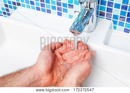 Point of view shot of a man washing his hands in a bathroom sink