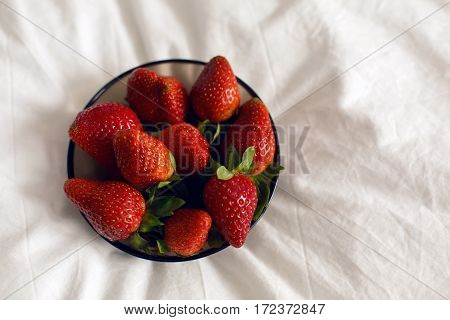 black transparent plate with fresh strawberries on a white bed