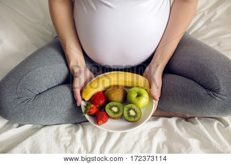pregnant girl holding a bowl of fruit sitting on a white bed