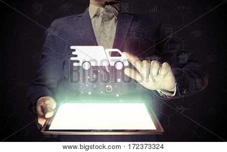Image of aman with tablet in his hands and car icon. Logistics concept delivery of cargoes and goods.