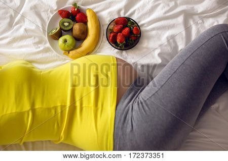 pregnant girl holding a bowl of fruit lies on a white bed