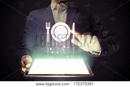 Image of a man with tablet in his hands and food restaurant icon. He looking menus ordering food delivery rate restaurant with using online services.