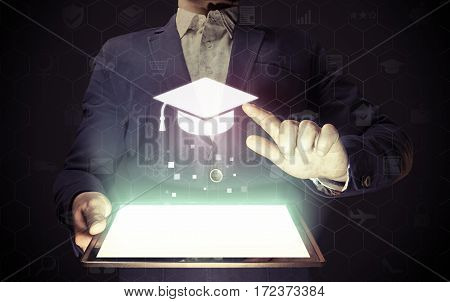 Image of a man with a tablet in his hands. He presses on the icon graduation hat cap. Online education concept choose of career.