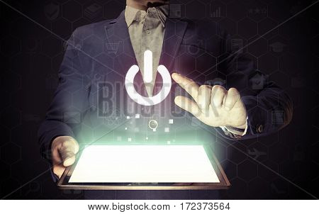 Image of a man with tablet pc in his hands. Finger touches the power button icon. ON- OFF concept of something.