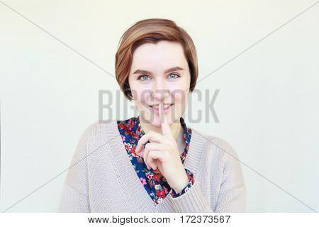 Girl Holds A Finger At Lips. The Sign Of Silence Or Secret.