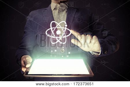 Concept of scientific and educational online service. Man touches to the atom icon. He holds tablet pc that contains a many different online services.