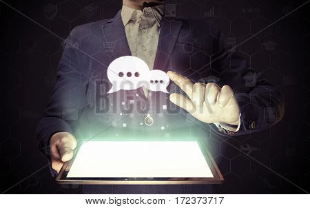 Image of aman with tablet in his hands and speech bubbles icon. Communication and technology concept. Сorporate сhat feedback support service.