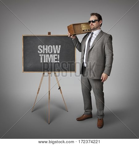 Show time text on blackboard with businessman holding radio