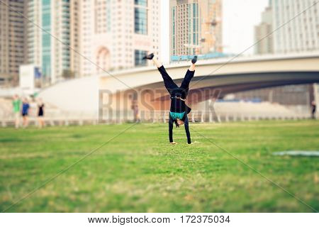 tourist to dubai having fun, doing a cartwheel on a small meadow at dubai marina