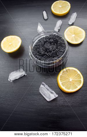 Black Caviar On Black Background With Slices Of Lemon And Ice