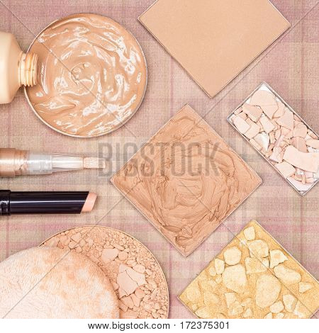 Makeup products to even skin tone and complexion: concealer stick, highlighter, foundation, compact and shimmer golden powder