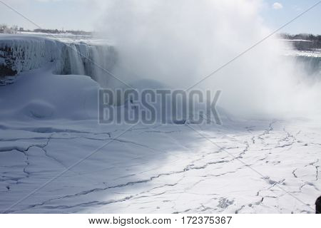 Niagara Falls, mist rising almost covering the falls from sight during winter months. Ice formed above, below, and beside rushing waters.