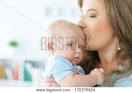 young woman holding baby boy and kissing him