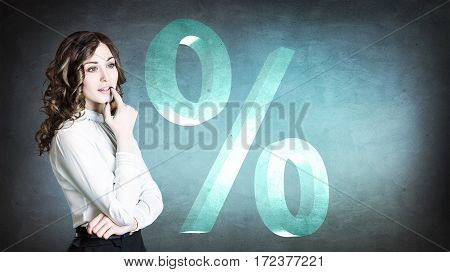 Businesswoman looking on big virtual percent over blue background.