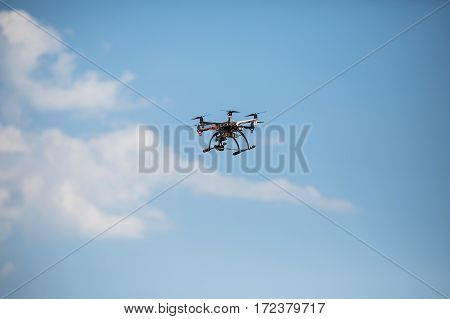 Helicopter with a professional camera flies over the trees against a blue sky. Dron.