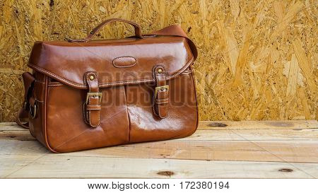 brown leather bag  for men on wooden floor.