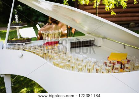 Beautiful wedding ceremony outdoors. Glasses with champagne standing on the piano buffet.