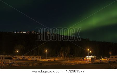 BJORKLIDEN, SWEDEN ON SEPTEMBER 20. View from the parking lot downhill the Hotel Fjallet on September 20, 2016 in Bjorkliden, Sweden. Aurora borealis, Northern Lights above the Hotel. Caravans this side. Editorial use.